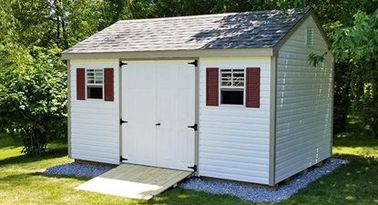 A white vinyl shed with dark red shutters