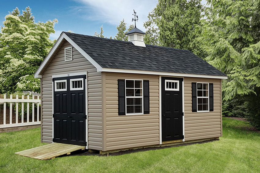 A tan shed with black doors and vinyl shingles